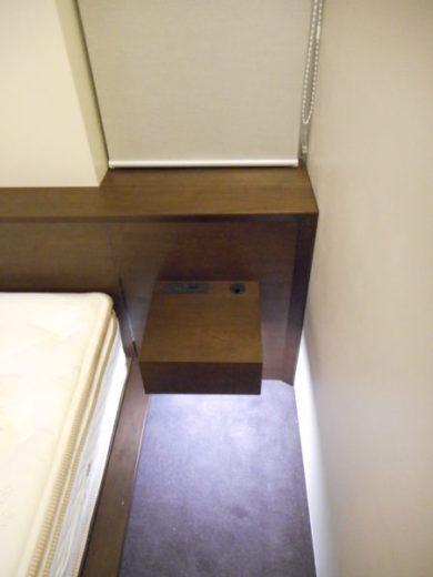 右側のナイトテーブルと寝室の小窓